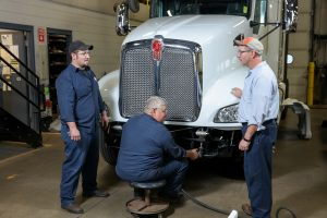 mechanics working on truck bumper