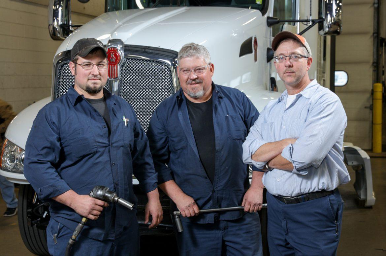 three fleet mechanics standing near semi truck