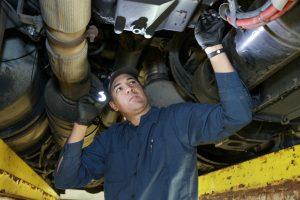 diesel mechanic inspecting under semi truck