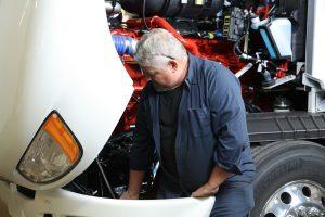 diesel mechanic inspecting under semi truck hood