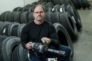 diesel mechanic in front of tires