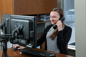 about us office help desk employee on the phone at the desk